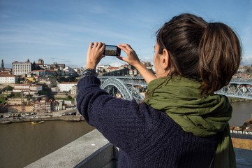 Young woman taking pictures of Oporto cityscape