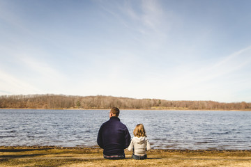 Man and girl sitting together by a body of water