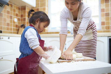 little asian girl making paste in kitchen with her mother