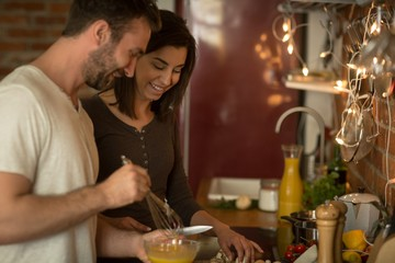 Happy young couple preparing food at home