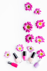 Choose nail polish for manicure. Bottles of colored polish on white background top view copyspace