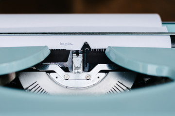 "A retro blue typewriter with the word begin typed on the paper"" retro blue typewriter wi"" retro blue typewriter with the word begin"" typ""""retr"""""" retro blue typewriter with the word begin typed on the paper"""" retro blue typewrit""""retro blue typewriter"""