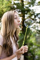 Beautiful teenage girl blowing bubbles