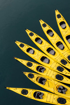 yellow sea kayaks tied together in water