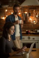 Man having drink while woman using laptop