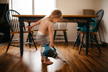 Toddler cleaning floor with handheld vacuum