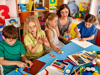 Plasticine modeling clay in children class. Teacher teaches kids together play dough and mold from plasticine in kindergarten or preschool. Group of four people. Zoo from the clay.
