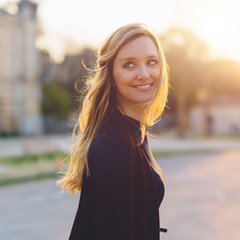 Beautiful blond woman at sunset in the city