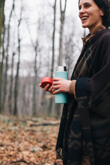 Happy woman holding a thermos