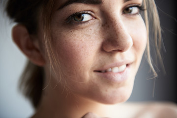 Young freckled woman looking at camera