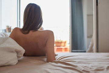 Topless brunette with moles on back lying on bed
