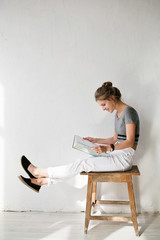 Young beautiful blonde woman reading a book