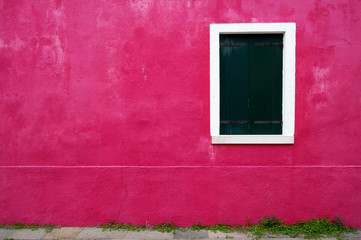 Green window on a pink house in Burano, Italy