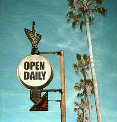 aged and worn vintage photo of open daily sign