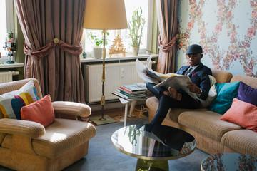 Stylish Elegant Young Black Man Reading Newspaper in Beautiful Living Room