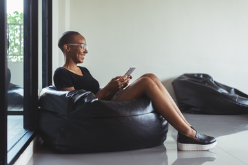 African American Woman in a Bean Bag Using Tablet