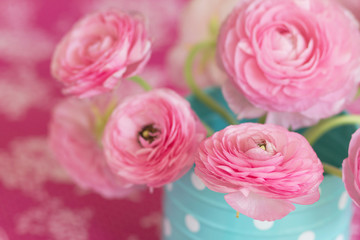Pink ranunculus flower in blue watering can