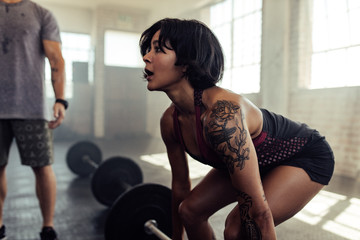 Determined young woman training with barbell at gym