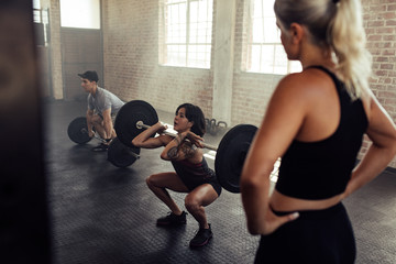 Woman lifts barbell with personal trainer