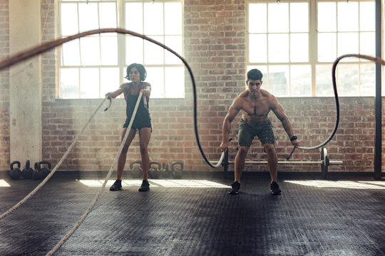 Young people doing intens workout routine with ropes