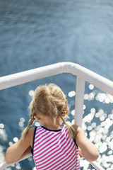 Beautiful young girl traveling on a ship and looking over the deck