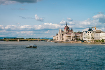 The Hungarian Parliament Building on the bank of the Danube in Budapest. Sunny day with clouds