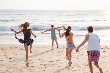 Shiny happy people - four friends having fun at the beach