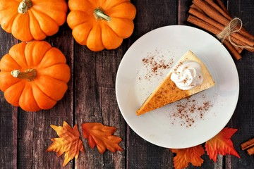 Slice of pumpkin cheesecake with whipped cream, top view on a rustic wooden background