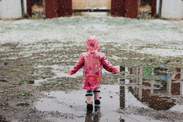 Toddler girl in a pink raincoat jumping in big mud puddles.