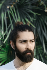 Portrait of a mixed race man in front of some palm leaves