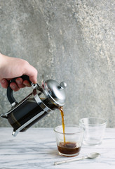 Hand pouring coffee from a cafetiere into a glass.