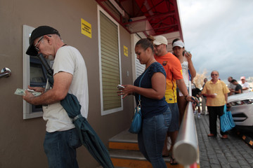 People queue to get money from an ATM after the island was hit by Hurricane Maria, in San Juan