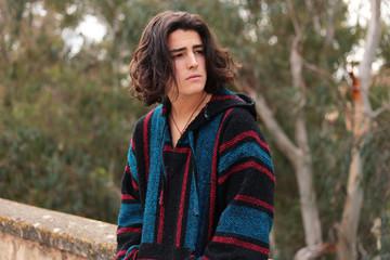 Bohemian teenage boy with long hair outdoors