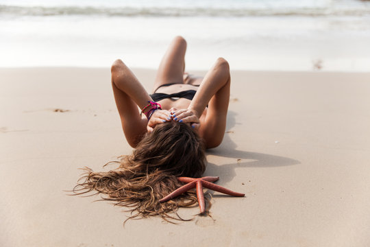 Beautiful woman at the beach with the starfish in her hair