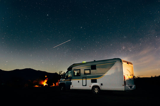 man by campfire near motorhome with night sky