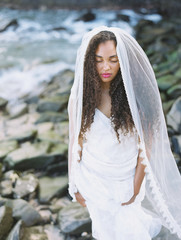 beautiful black bride on beach in gorgeous wedding gown with rocks and ocean
