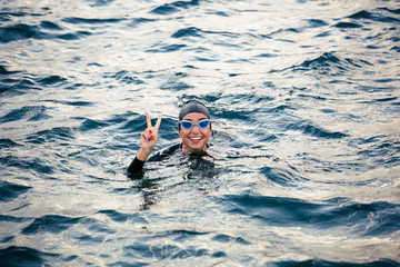 Smiling woman doing victory sign in the sea.