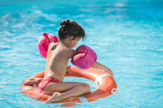 Little girl in a swimming pool floating on a lifebelt