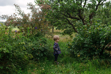 Child stands peacefully in a wild garden.