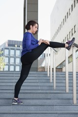 Woman checking time while performing stretching exercise outside