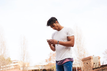 Young man with dark-hair using cell phone