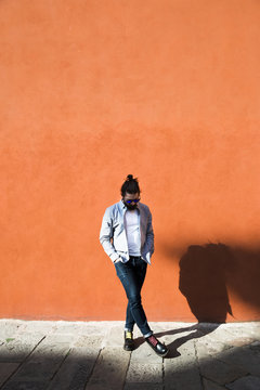 Man kicking away a stone in front of an orange wall