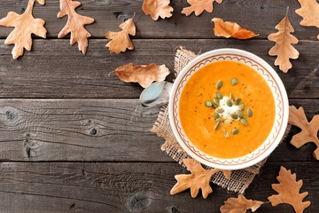 Creamy butternut squash soup, overhead table scene with fall leaves on a rustic wood background