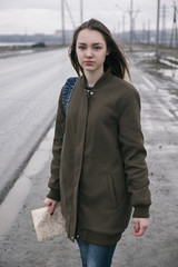 Portrait of beautiful long-haired woman with map and backpack on road