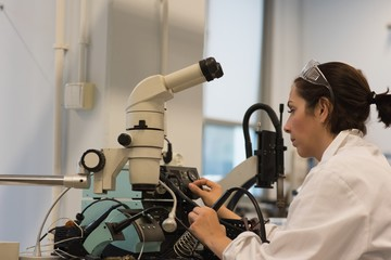 Female technician researcher looking through microscope