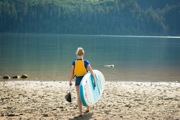 Rear view of woman carrying paddleboard and oar