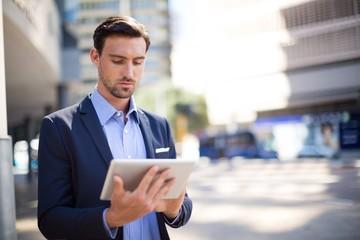 Businessman using digital tablet near office building