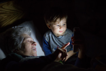 Grandmother with her grandson looking a smartphone in the dark