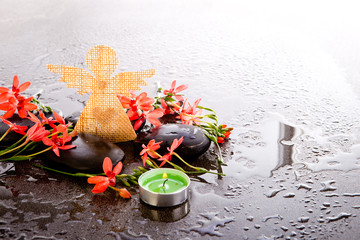 Orange Red Freesia Laxa flowers with black massage stones, green tealight candle and burlap angel with hearts