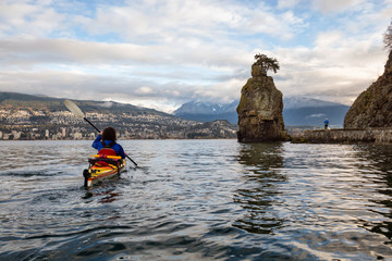 Kayaking near the Stanley Park with a man running on the seawall. Picture taken in Vancouver, British Columbia, Canada, during a cloudy winter morning.